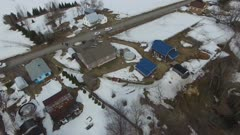 Drone flying over landslide in winter with rural houses