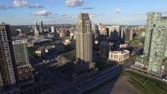 Drone flying close and around highrise building on sunny day
