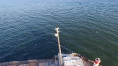 Overhead drone view of birds protecting their nest atop a boat mast off a wreck