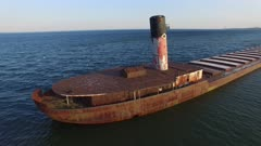 One minute extended sequence of drone flying along rusty cargo ship wreck