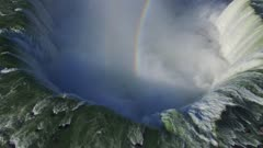 Gliding drone shot of waterfalls with double rainbows