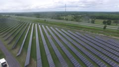 Multiple solar panels seen from a drone in flight next to highway