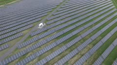 Very slow steady aerial shot of renewable energy plant with solar panels