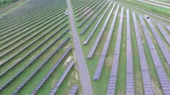 Slow drone reveal shot of solar farm next to a freeway in the countryside