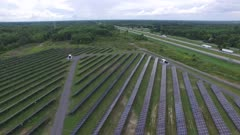Two small structures in solar power farm next to multiple solar-panels