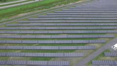 Large-scale solar power farm established in rural field viewed by drone