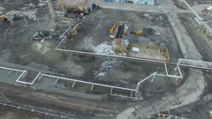Reveal and rising drone shot of huge industrial yard with train moving