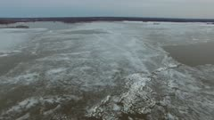 Aerial extended shot of ice plates floating in large river during spring