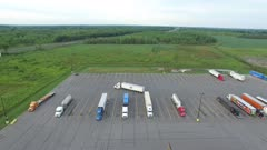 Wide truck stop viewed by drone while semi backs up into parking space
