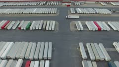Geometrical drone view of truck driving thru multiple parked cargo vans