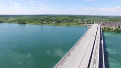 Drone flying very slowly sideways over water power generating plant in Canada