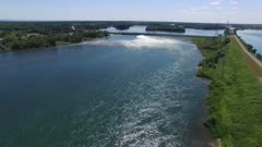 Extended sequence of drone flying towards power dam making major swirl