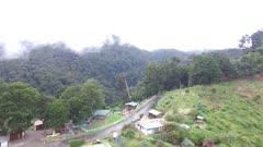 Aerial backwards flight over mountainous terrain in tropical setting
