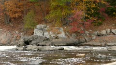 Beautiful fall foliage seen on pan shot that goes along the river shore