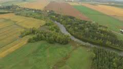 Rural farmlands with river running through and trees growing on each edge
