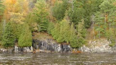 Dramatic charcoal colored vertical rocky shores of a river during autumn