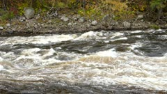 Rapid white river flow cascading on rocks while current brings it down a valley