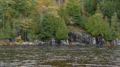 Strong river current carries water along the rocky shores of a mixed forest in fall