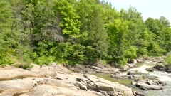thick woods stone outcrop calm riffle between panning right