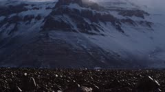 Sun shines through snow mist blowing off rock cliffs and glacier headwall of mountains in Antarctic Dry Valleys