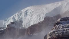 Snow mist blowing off rock cliffs and glacier headwall of mountains in Antarctic Dry Valleys