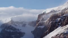 Snow mist and clouds blowing off rock cliffs and glacier headwall of mountains in Antarctic Dry Valleys