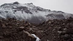 Rock pile formations with snow and glacier mountains in background in Antarctic Dry Valleys