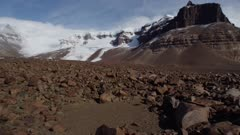 Rocky valley terrain with snow mist and glacier mountains in background in Antarctic Dry Valleys