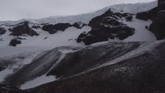 Glacier coming over mountain peaks with snow mist blowing off headwall and cliffs in Antarctic Dry Valleys