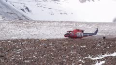 Research helicopter with spinning propellers on rocky valley terrain in Antarctic Dry Valleys