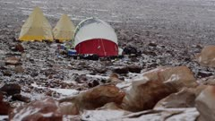 Snow covered research camp tents and sandstone rock terrain in Antarctic Dry Valleys
