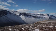 Pan of Olympus Range and research helicopter on rocky terrain in the Antarctic Dry Valleys