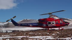 Red helicopter on the rocky terrain in Antarctic Dry Valleys