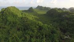Aerial over jungle covered hill, rivers and mangroves at sunset