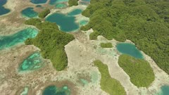 Aerial drone shot of shallow basins, coral communities and rock islands of Palau, camera tilts up to show fringing reef and horizon