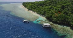 Aerial shot descending towards tourist boats, coral reef and island