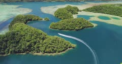 Aerial shot following boat speeding through rock islands of Palau