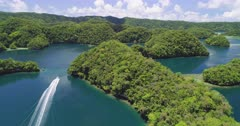 Aerial shot following boat through tropical islands and channels in Micronesia