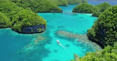 Aerial shot of boat slowly travelling through tropical lagoon and Rock islands in Palau