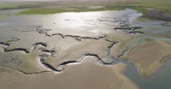 Aerial shot descending towards large intertidal mudflat with drainage channels in coastal South West England