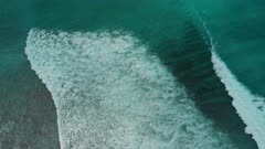Aerial shot of oceanic waves breaking and curving onto shore