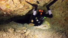 Cave diver with sidemounted tanks swims into tight restriction in cavern