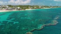 Aerial shot tracking along coastline over coral reef in Bermuda