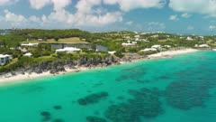 Aerial shot tilting up from coral reef to coastline of Bermuda