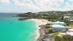 Aerial shot tracking along southern coastline of Bermuda towards beach