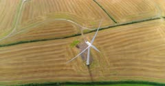 High angle reversing view and reveal of three wind turbines in the UK