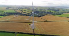 Aerial push in to three wind turbines in the UK