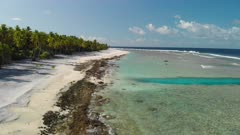 Aerial shot travelling down coastline of Nikumaroro Atoll in Kiribati