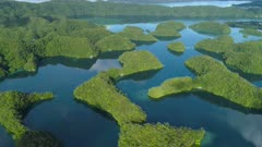 Aerial shot Palau Rock islands on very calm morning with calm water reflecting sky