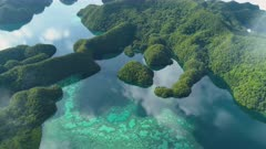 Aerial shot low clouds reveal Palau Rock islands on very calm morning with calm water reflecting sky